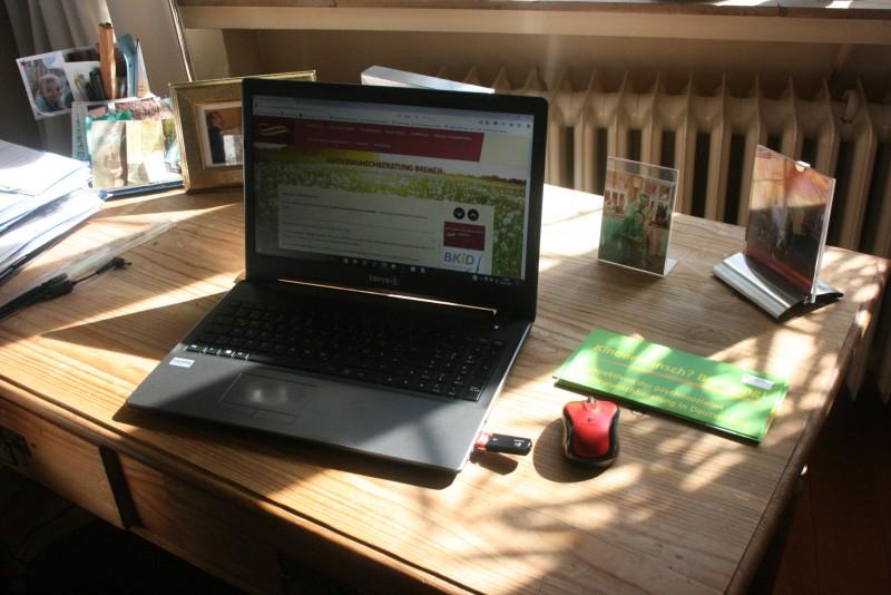 Laptop auf Holztisch für Online-Sprechstunden