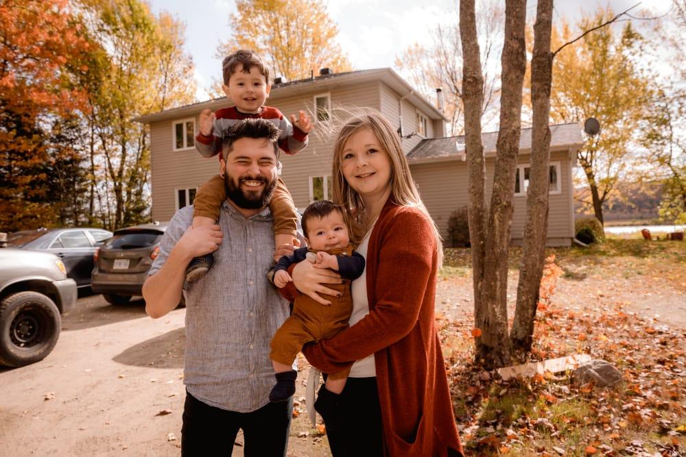 Glückliches Paar mit Kindern in den Armen, vor einem Haus stehend.
