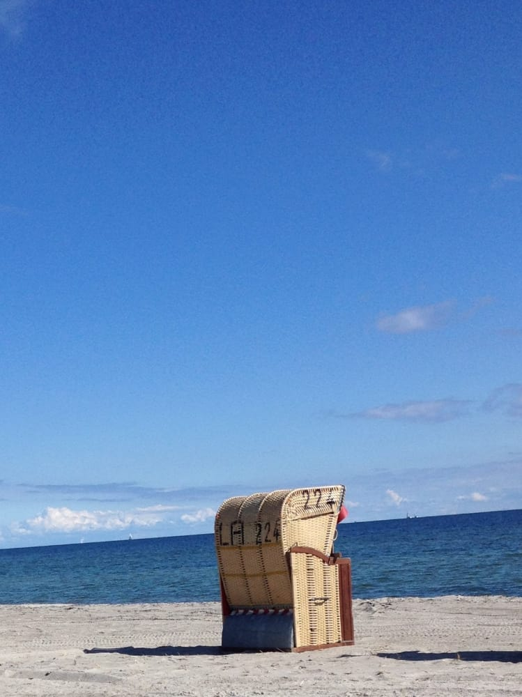 Einzelner Strandkorb vor blauem Himmel